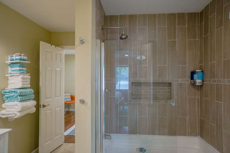 a large tiled shower with glass doors and a towel rack to the right