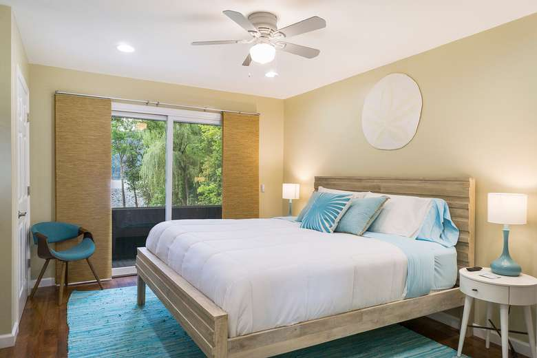 a bedroom with a large bed, nightstand, lamp, ceiling fan, chair, and sliders to an outside deck