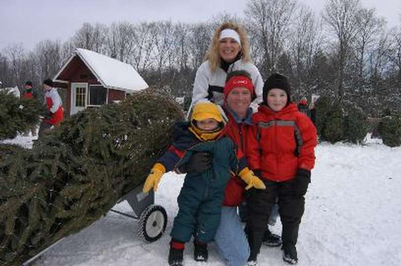 a family of four posing in front of a fresh cut christmas tree