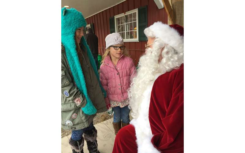 santa meeting with two girls at a farm