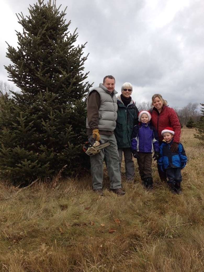 a family standing in front of a tall christmas tree outside
