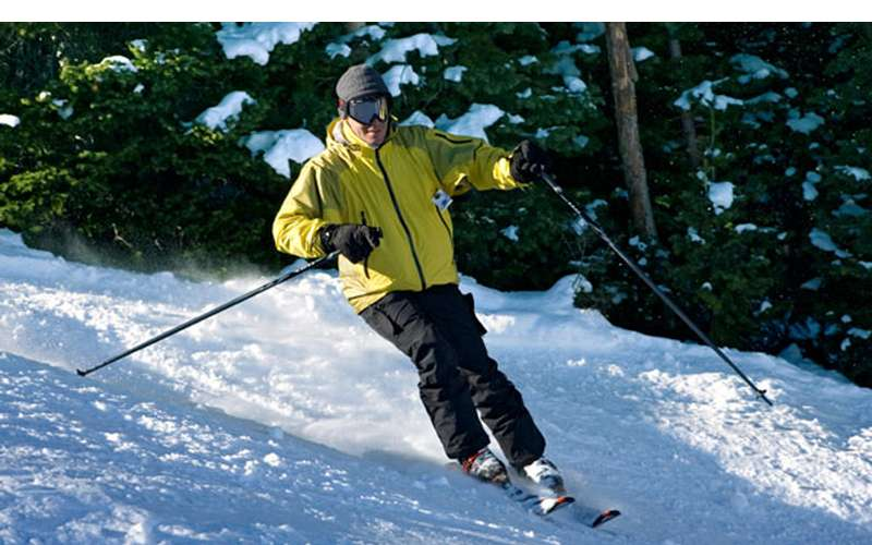 a skier in a yellow jacket going downhill