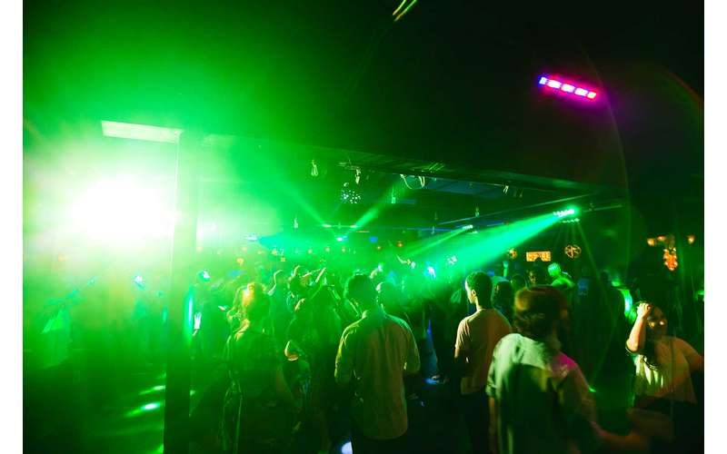 bright green lights shining over a dance floor and music venue