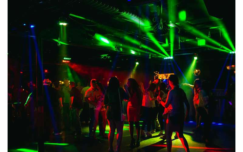 colorful lights flashing on the dance floor in a nightclub