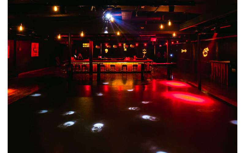 a wide open dance floor with lights on and a bar in the background