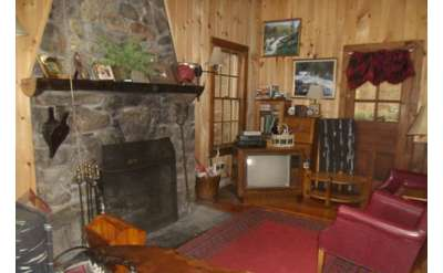 a large stone fireplace inside a camp style living room