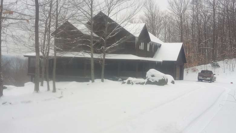 a large brown house covered in snow, a truck is outside near the garage