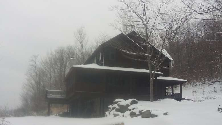 a side view of a large brown house during a snowy winter day