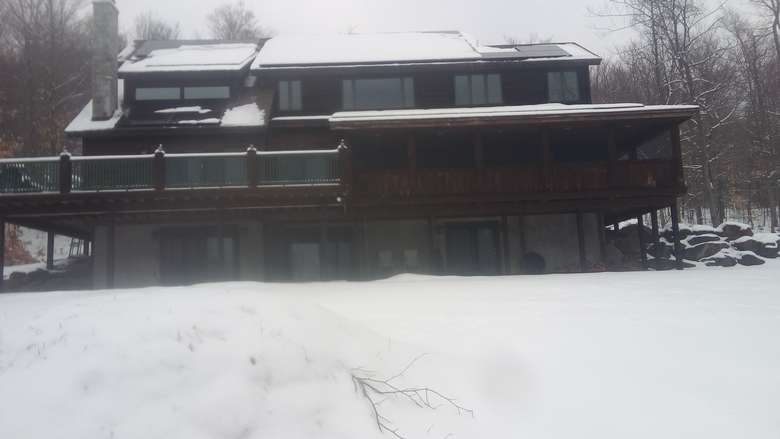 view of a porch and deck on a brown house during a snowy winter day