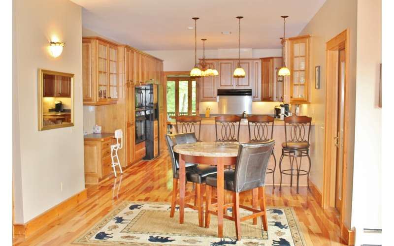 a large kitchen with wooden cabinets and flooring, a counter, fridge, and more
