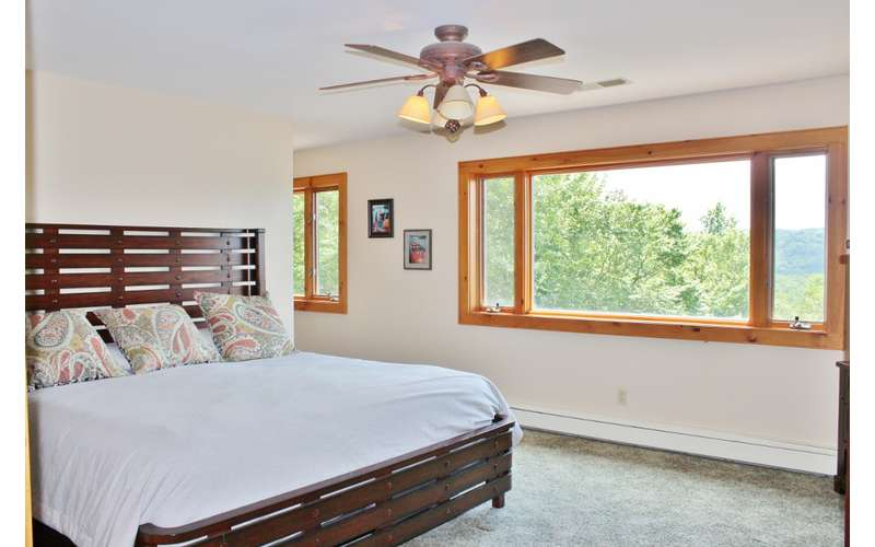 a bedroom with wide windows and a ceiling fan