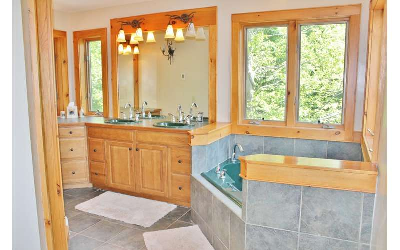 a large bathroom with a jacuzzi tub and sinks in the back