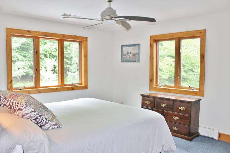 a bedroom with multiple windows and a ceiling fan