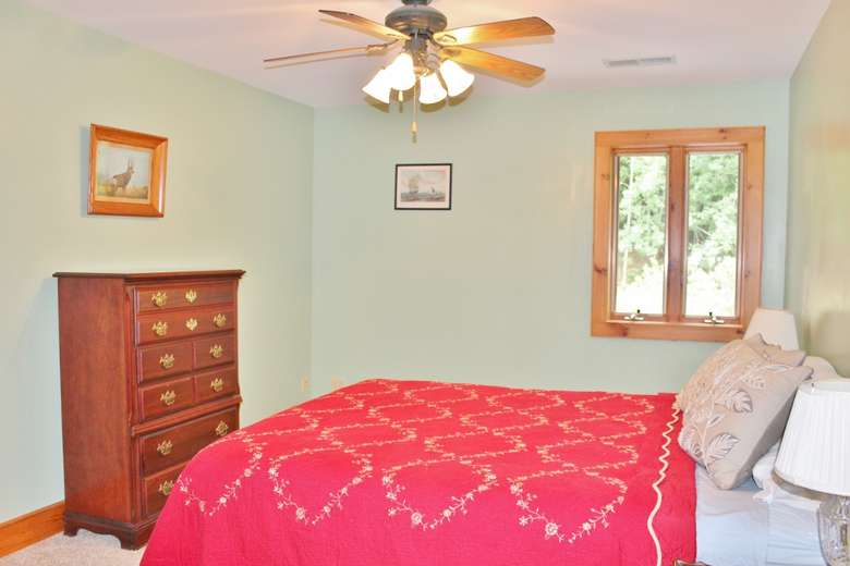 a bedroom with pink blankets on the bed, a dresser, and a ceiling fan