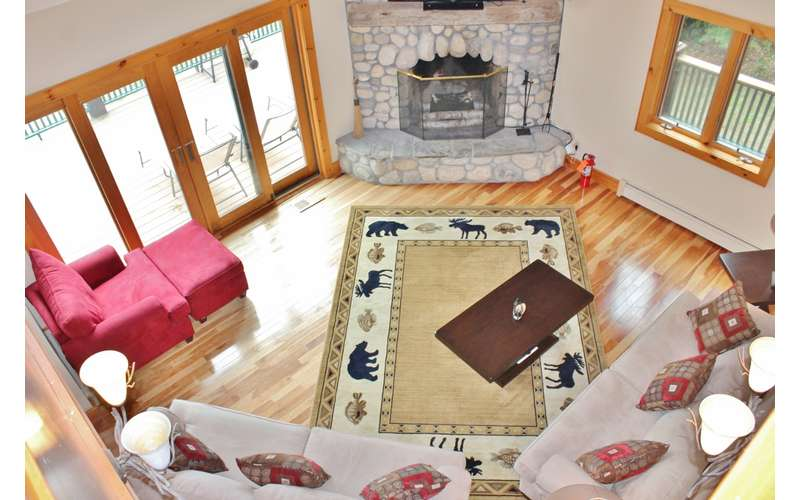 an aerial view of a living area with an adirondack themed carpet, couches, and a stone fireplace