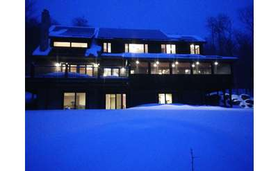 large home covered in snow in the evening