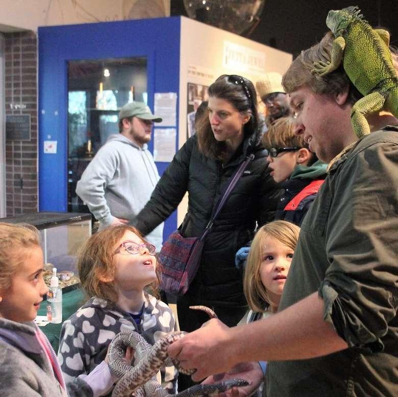 man with iguana on his head, kids crowding around