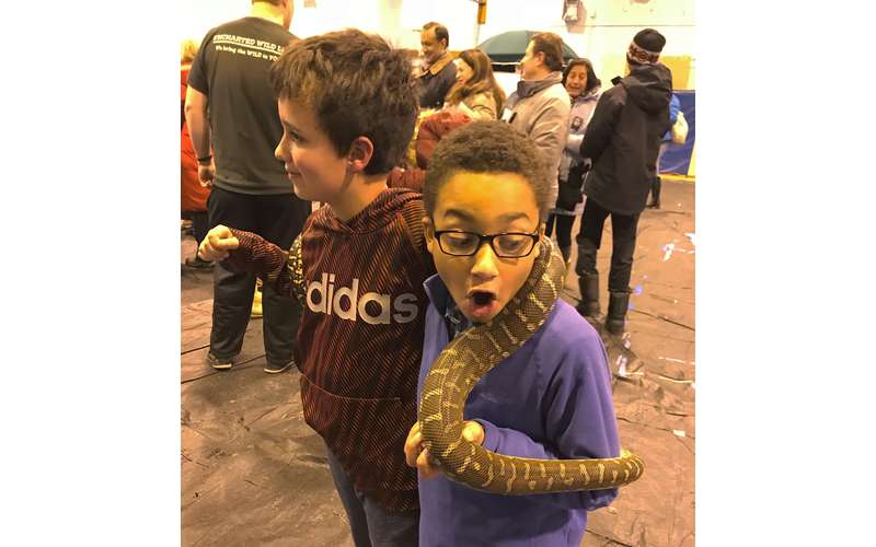 two little kids holding a snake