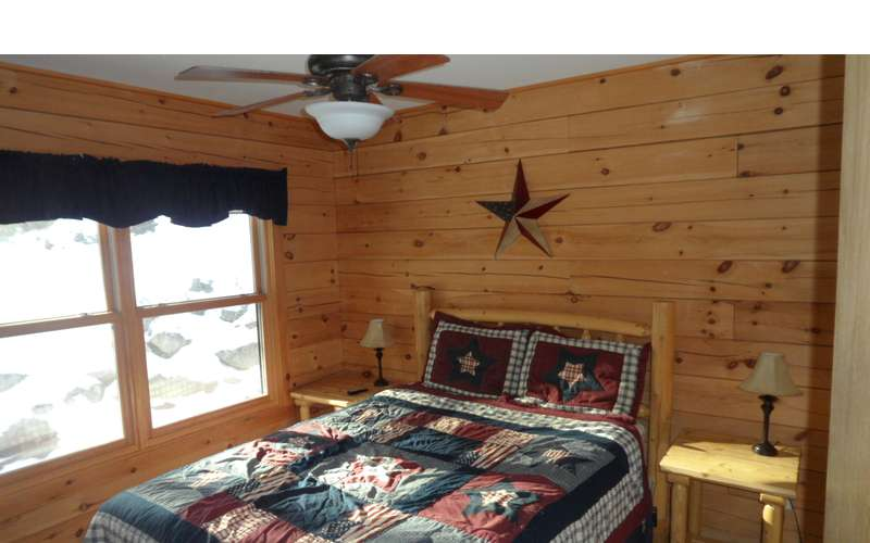 a different bedroom with wood panel walls and a window, a ceiling fan, and more
