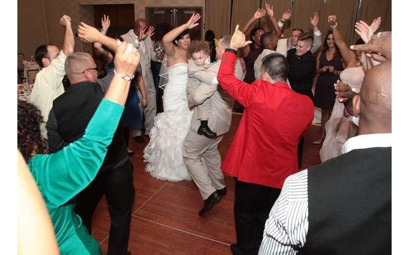 people cheering while bridge and groom dance