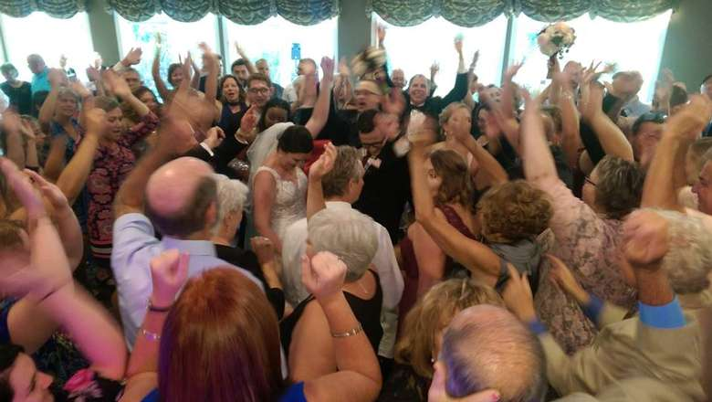 large crowd of people around a bride and groom