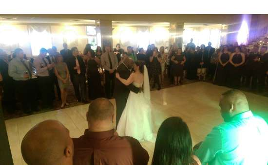 bridge and groom dancing on the floor surrounded by guests