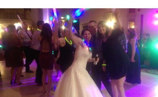 a bride waving at a wedding dance party