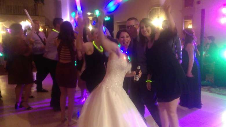 a bride waving at a wedding dance party