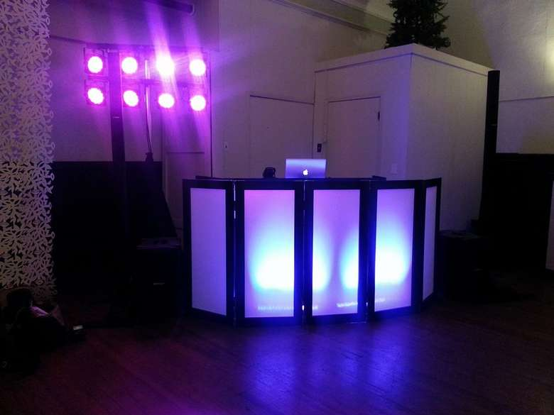 a dj booth with bright purple lights in the back
