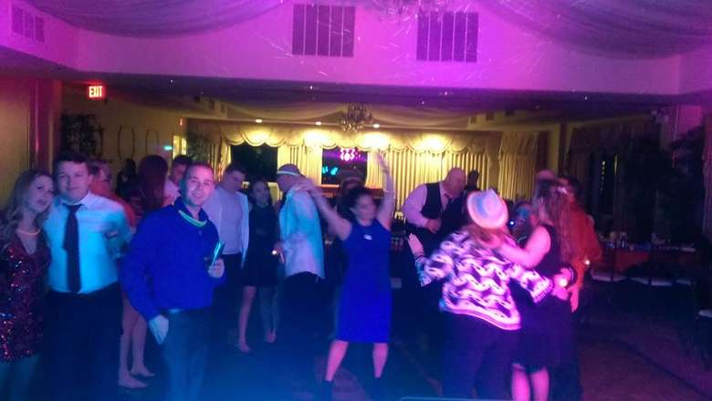 people dancing in a small venue with colored lighting