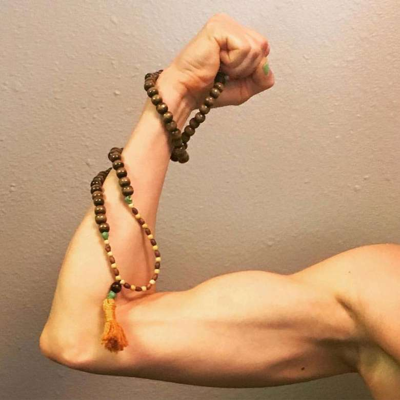 an arm flexing with beads wrapped around it