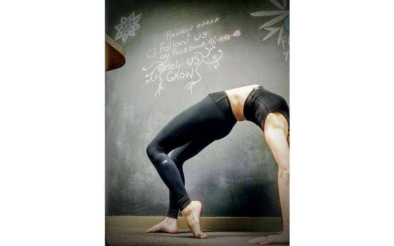 woman doing a back bend in front of a giant chalkboard
