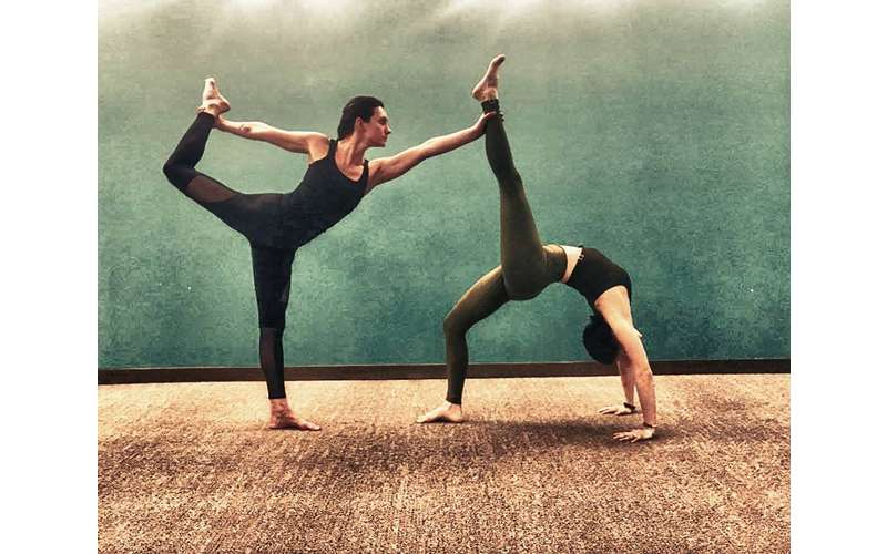 A Variety Of Classes For All Levels Is Offered At Hot Yoga Queensbury PrevNext Two People Practicing Poses
