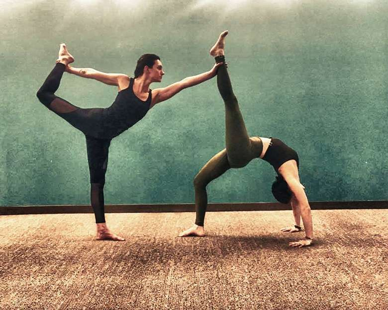 two people practicing yoga poses together, one in standing bow and the other in wheel