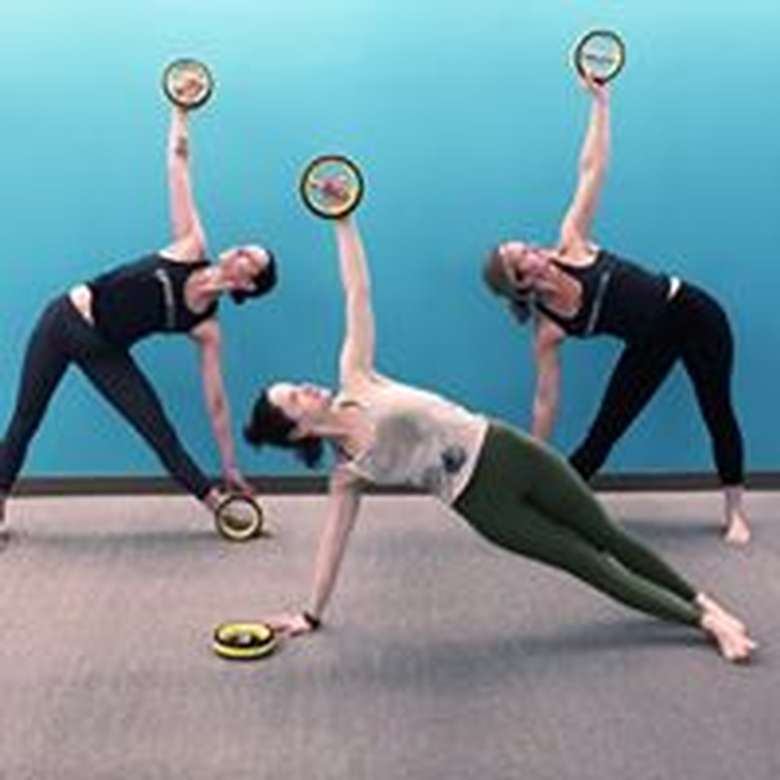 three women doing yoga while holding up circular objects