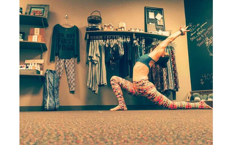 a woman bending back in a low lunge in front of clothes