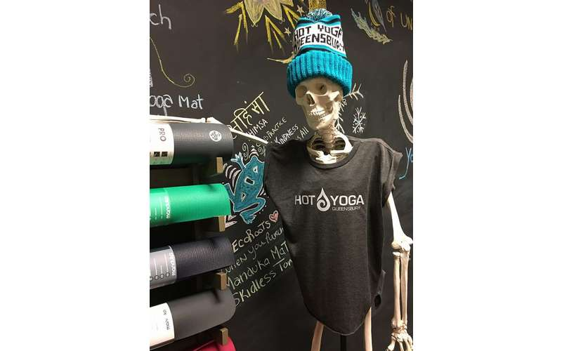 a skeleton wearing a hot yoga shirt and hat