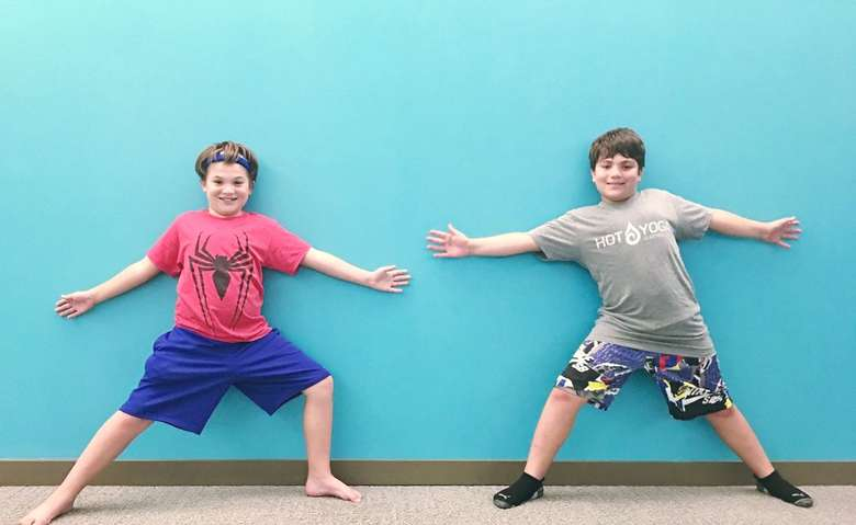 two kids in front of a teal blue wall