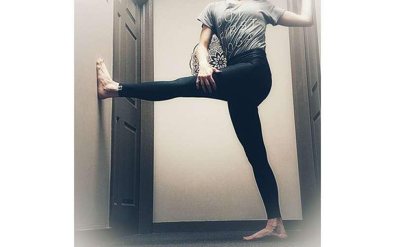 a woman stretching her leg near a door