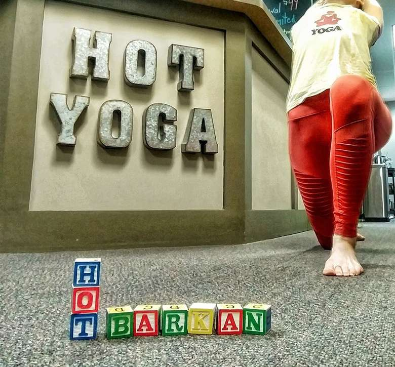 woman doing a high lunge in front of a desk that says Hot Yoga and blocks in front of her that say Hot Barkan