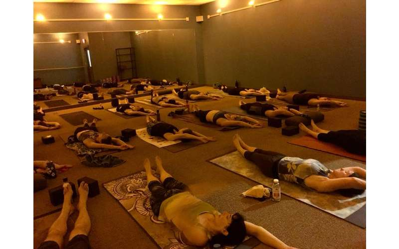 a group of people practicing yoga together, lying on their mats