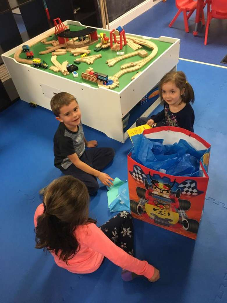 toy train set in the background, and there are three kids near a large birthday bag
