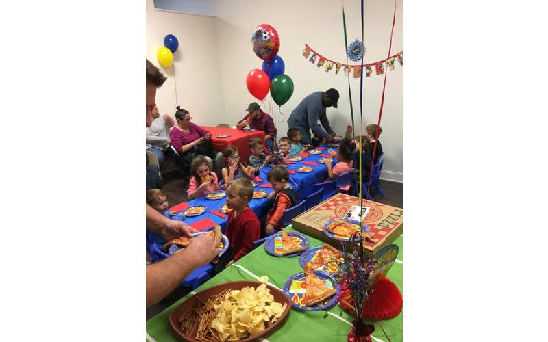 a birthday party table with pizza and chips nearby