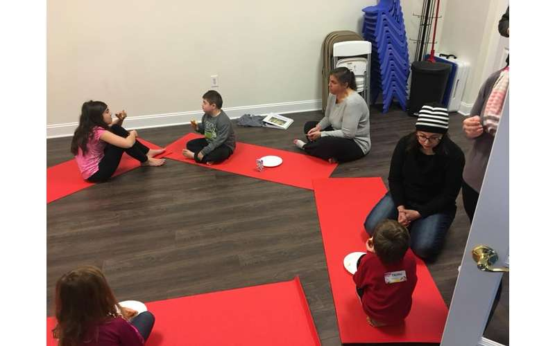 kids and adults sitting on red yoga mats