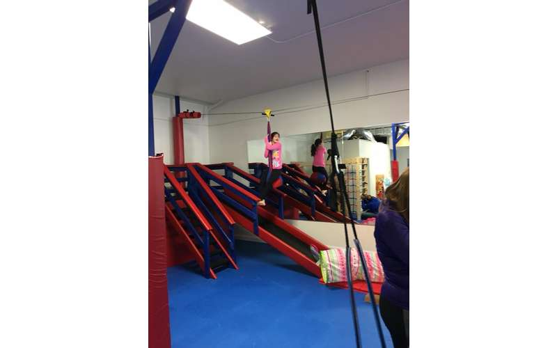 a girl riding down an indoor zip line