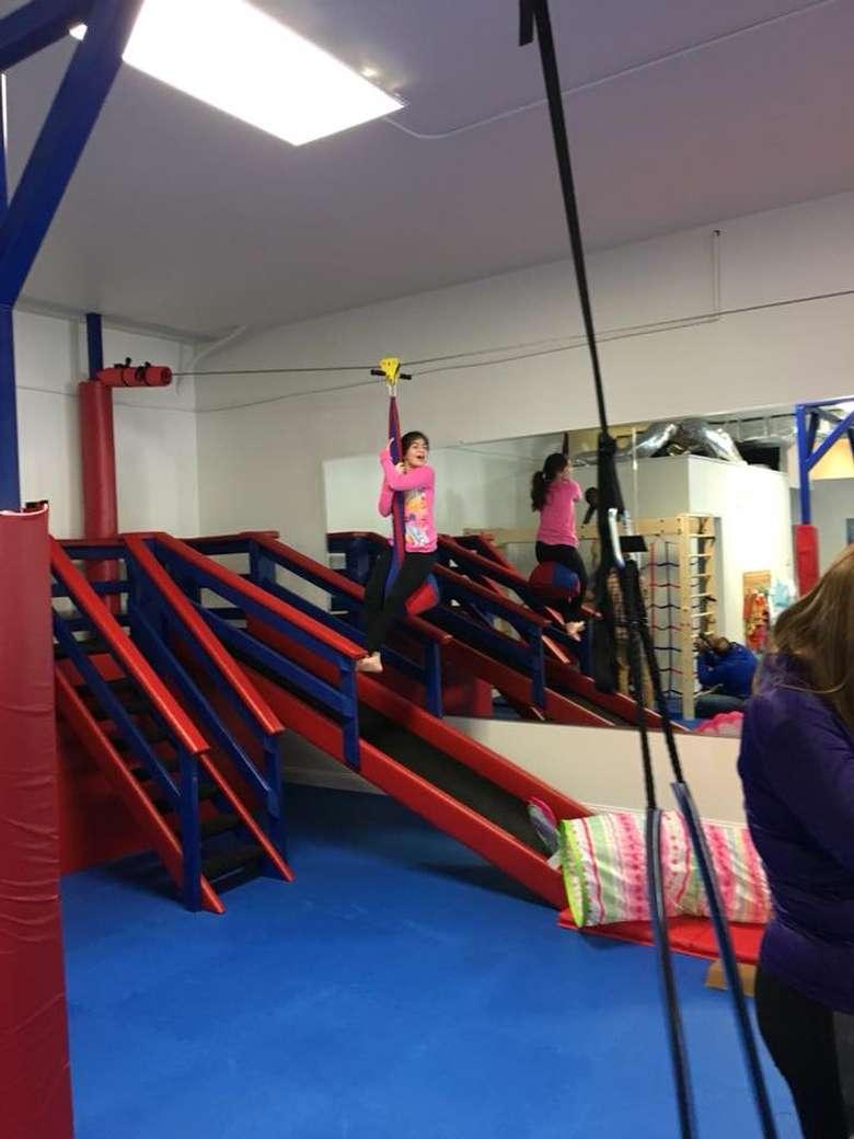 a girl riding down an indoor zip line