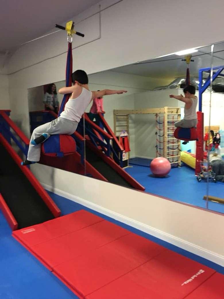 a kid riding an indoor zipl ine over a small mat