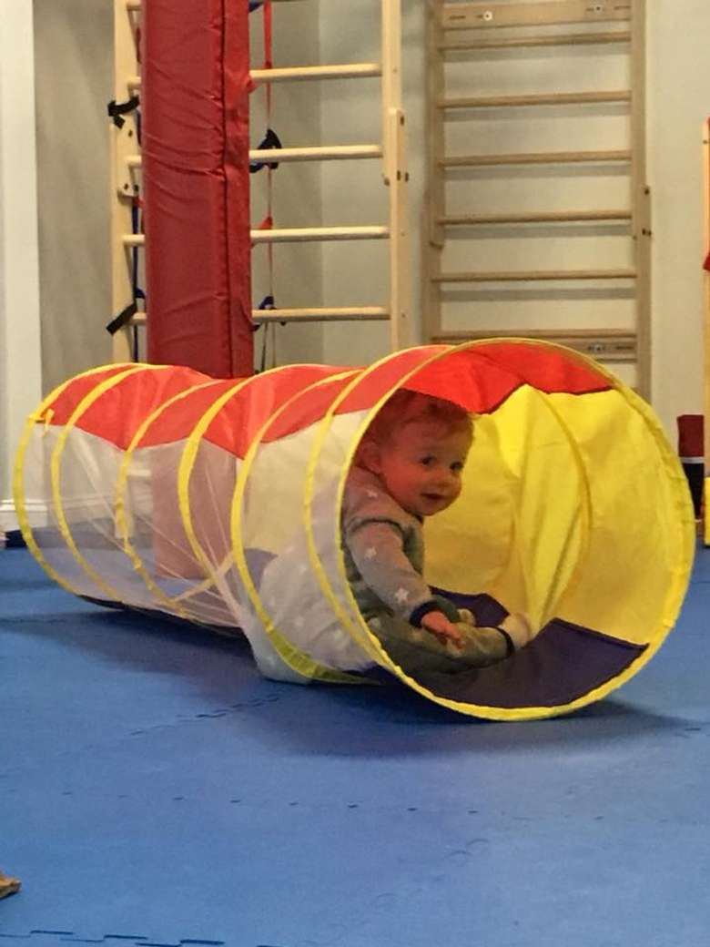 a young kid inside a tunnel in a play area