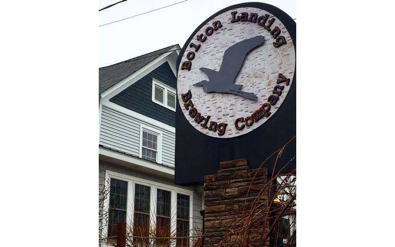 the sign for bolton landing brewing company in front of a building