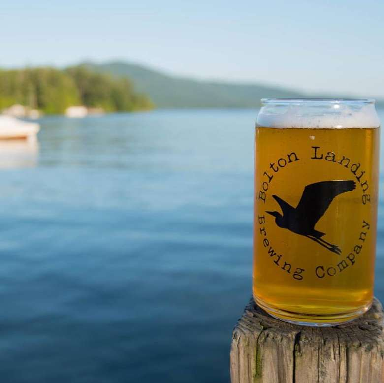 a glass of beer on a dock with the bolton landing brewing company logo on it